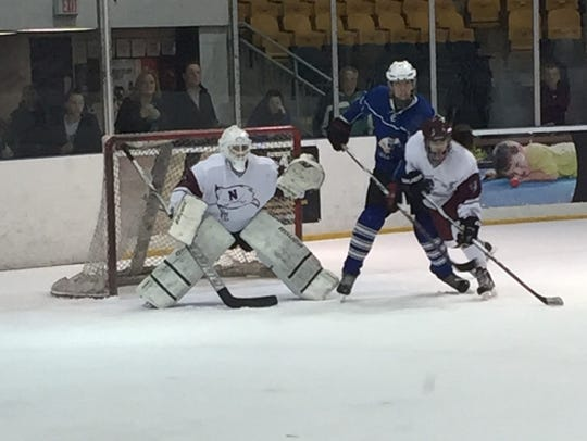 Millburn's Spencer Brown (middle) trying to create