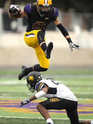 Hardin-Simmons wide receiver Reese Childress (21) hurdles East Texas Baptist cornerback Grant LaPoint-Teate (29) during the first quarter of the Cowboys' 66-30 win in 2016 at HSU's Shelton Stadium.