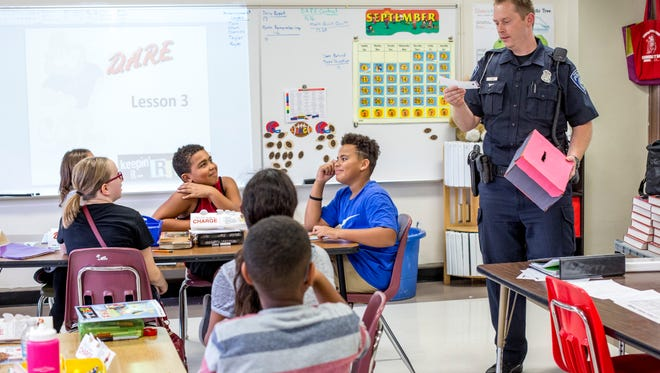 Patrick Eash, a community services officer with the Port Huron Police Department, answers students' questions as he leads a D.A.R.E. activity with a fifth-grade class Wednesday, September 28, 2016 at Garfield Elementary School.