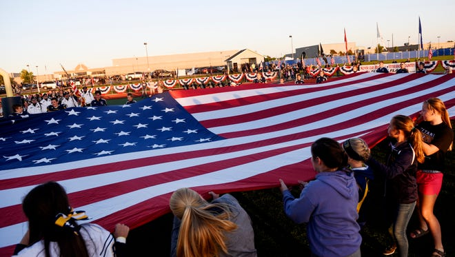 Tea students hold a giant American flag during the national anthem before the first half of their high school football game on Friday, Sept. 29, 2017, in Tea.