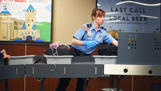 Lizbeth Hochhalter, training instructor, checks bags for any electronic devices at the Sioux Falls Regional Airport. in February. The Transportation Security Administration, TSA, informed passengers of the new carry-on screening procedures before they went through security. The new procedures will be implemented at every airport nationwide by late spring.