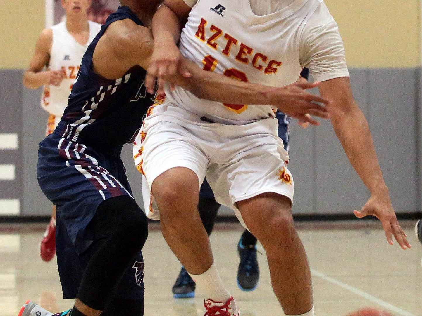 Travis Hamman of La Quinta (navy, left) reaches in while defending Joey Fabela of Palm Desert (13, white, bottom) with 6:10 left to play in the fourth quarter with La Quinta up, 43-41 on Thursday, February 12, 2015 at Palm Desert.