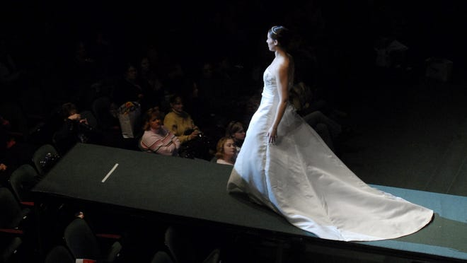 In the spot light, bridal fashion show model walks the runway wearing a gown by Maggie Sottero. Hundreds of women, and a few of the men they love, gathered at McMorran Place for the Annual Bridal Show hosted by RadioFirst.