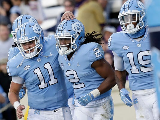 North Carolina quarterback Nathan Elliott (11) congratulates Jordon Brown (2) with Dazz Newsome (19) following Brown's touchdown against Western Carolina during the first half of an NCAA college football game in Chapel Hill, N.C., Saturday, Nov. 18, 2017. (AP Photo/Gerry Broome)