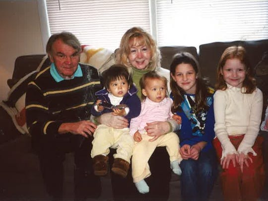 Ed and his wife Mary Murray holding grandchildren: