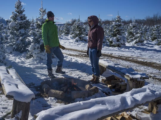 Joe and Carol Parr, from Charlotte, warm up a bit by a fire after cutting down a tree at the Peacock Road Family Farm,  Nov. 21, 2015.
