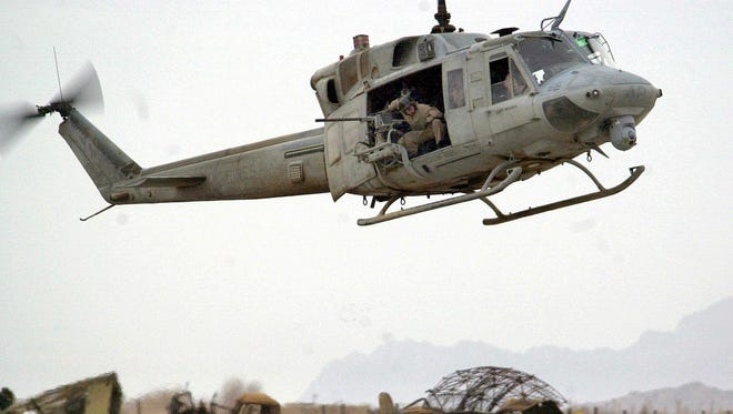 A U.S. Marine UH-1 Huey helicopter flies over wreckage left over from U.S. bombing raids at Kandahar airport in December 2001.