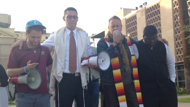 From left, Johnny Martin, Rabbi Dr. Shmuly Yanklowitz,  Pastor James Pennington and Rev. Reginald D. Walton, stand in solidarity to protest statements made by Arizona Gov. Doug Ducey on Monday. The group led a protest outside his office in downtown Phoenix on Wednesday, Nov. 18, 2015.