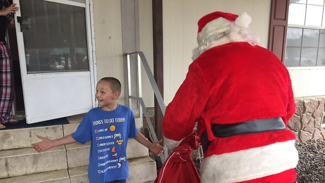 David, 10, was excited to get presents from Santa Claus on Wednesday. Santa, Grant Parish Sheriff Steven McCain and others delivered gifts and food to four families throughout the parish on Wednesday.