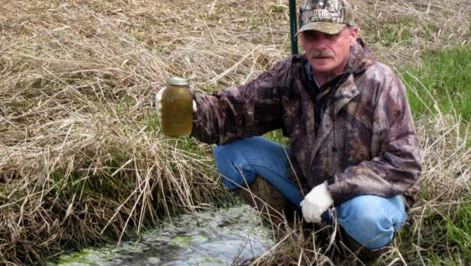 Terry Kafka of the DNR holds water sample of manure and liquid flowing from a farm field in Marathon County in 2014.