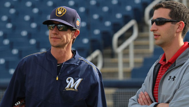 Brewers General Manager David Stearns and Manager Craig Counsell talk before a spring training game.