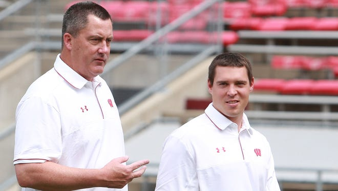 Wisconsin football head coach Paul Chryst (left) walks with Jim Leonhard