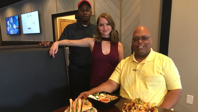 Felix Diaz, right, is general manager of The River's Edge Grill. Joining him in showing some of the restaurant's menu items are Daron Tillman, left, one of the cooks, and hostess Lindsay Spears.