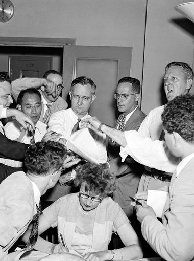 "Newsmen elbow their way in for copies of Korean Armistice Announcement at the State Department in Washington the night of June 29, 1951. As Lincoln White (upper right) of State Press relations tells them to ""come and get it."" The news was that Gen. Matthew Ridgway has asked communist commander in Chief in Korea to designate a representative to discuss an Armistice."