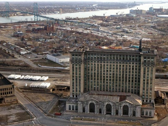 The massive abandoned and vacant Michigan Central Railroad depot rises above the landscape of southwest Detroit with the Ambassador Bridge