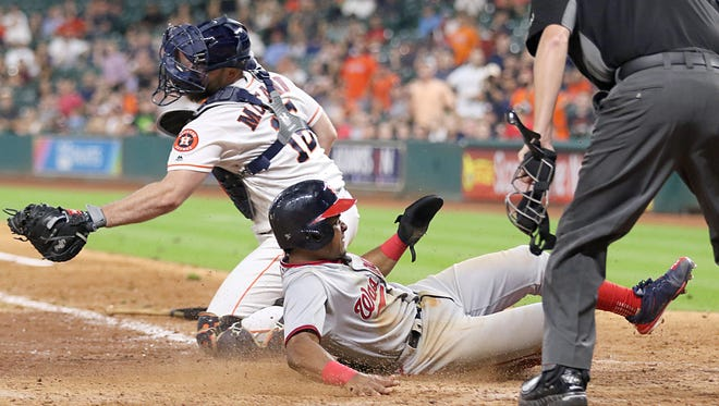 Nationals baserunner Wilmer Difo slides home safely in front of Astros catcher Brian McCann in the 11th inning at Minute Maid Park in Houston.