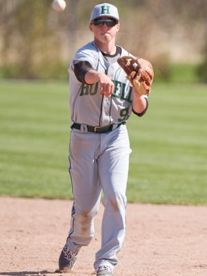 Howell's Justin Mercer throws out Fowlerville's Mitchell Hubert. At catcher, he started a triple play against Pioneer.