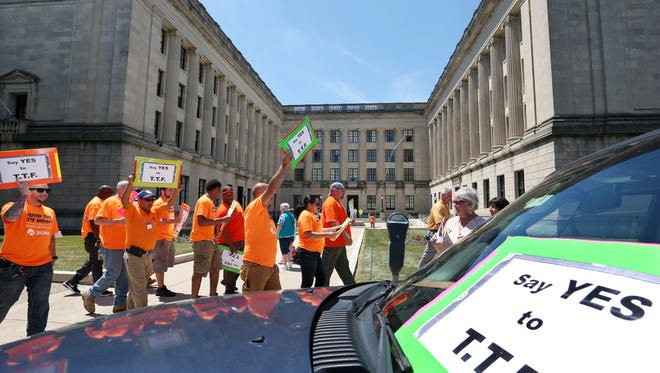 A large group of mostly construction workers hold signs and shout as they gather in front of the New Jersey Statehouse on Thursday urging passing of the transportation trust fund. The plan to swap a gas-tax hike for a gradual 1 percent drop in state sales tax is stalled in the Senate.