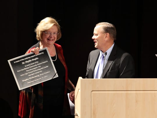 Phyllis Staplin, left, is presented with a plaque as the Staplin Performing Arts Center is dedicated in her honor on Nov. 12, 2015.