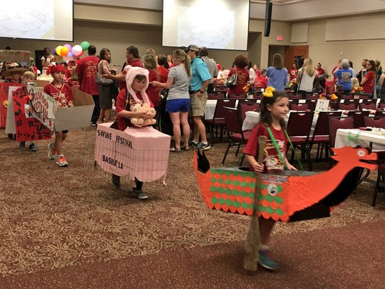 "Third-graders at Our Lady of Prompt Succor School parade Tuesday in their ""floats"" representing Louisiana festivals at the school's annual Louisiana Day celebration. The first float of the day represented Alexandria River Fete with a dragon boat."