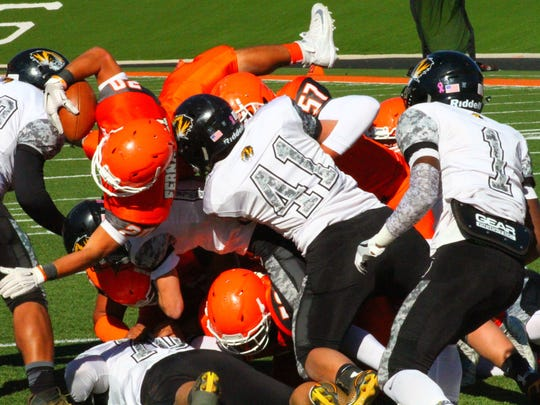 Artesia's Robert Fernandez dives over a pile of players into the end zone Saturday afternoon at the Bulldog Bowl.