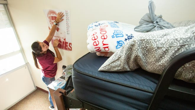New Mexico State Universty freshman Eliana Holguin, 18, left, moves into her dorm with the help of her mother Blanca, right, and bother Fernie, 10, on Saturday, August 11, 2018 during move-in weekend at Garcia Hall.