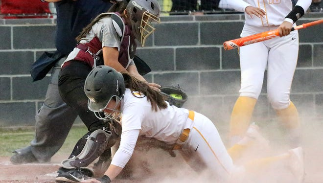 Alliese Medina of Parkland touches home plate before Andress catcher Yvette Solis could get the tag during their game Friday night at Parkland. The Matadors prevailed over the Eagles 5-4.