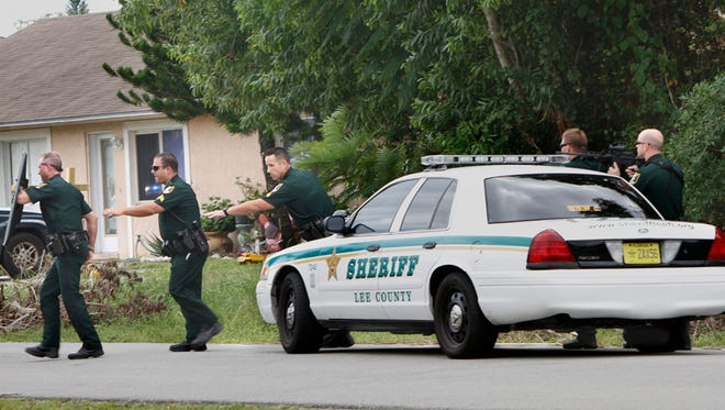Lee County deputies aim their weapons at an Ithaca Drive home in Fort Myers Thursday.