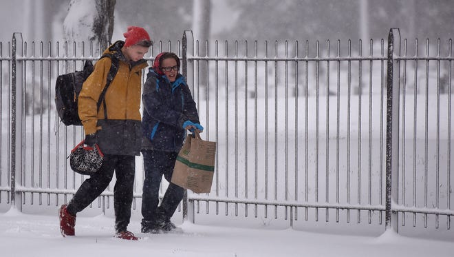 Noah Schiebout and Brendan Crawford walk to school along 26th St. on Friday morning in the snow.