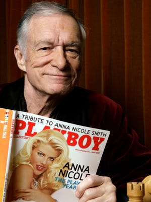 In this April 5, 2007 file photo, Playboy Enterprises founder Hugh Hefner poses with a copy of Playboy magazine featuring Anna Nicole Smith as Playmate of the Year, at the Playboy Mansion in Los Angeles. The magazine that helped usher in the sexual revolution in the 1950s and '60s by bringing nudity into America's living rooms announced this week that it will no longer run photos of completely naked women. Starting in March, 2016, Playboy's print edition will still feature women in provocative poses, but they will no longer be fully nude.