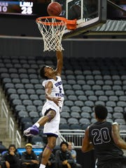 Lincoln Memorial's Luquon Choice looks on as Kentucky Wesleyan's Jordan Jacks goes up for a layup as Kentucky Wesleyan plays Lincoln Memorial in the second game of the Small College Basketball Hall of Fame Classic at the Evansville Ford Center Friday, November 18, 2016.