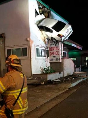 In this Jan. 14, 2018, photo provided by Orange County Fire Authority a vehicle that crashed into a building hangs from a second story window in Santa Ana, Calif.