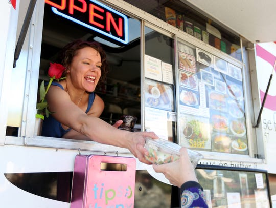 Carmen Nguyen hands a customer her order at the Fusion