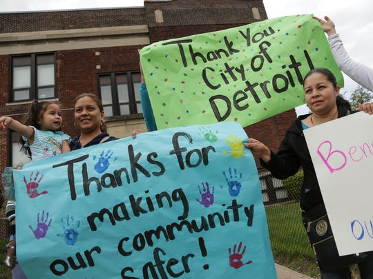 (left to right) Veronica Martinez of Detroit holds her Brittany Carbajal as Lucita Munoz and Irma Campos, hold signs thanking the city of Detroit as they watch the City of Detroit Construction Services workers tear down an abandoned structure across from Bennett Elementary School in Detroit on Thursday May 12, 2016 where there children attend school.