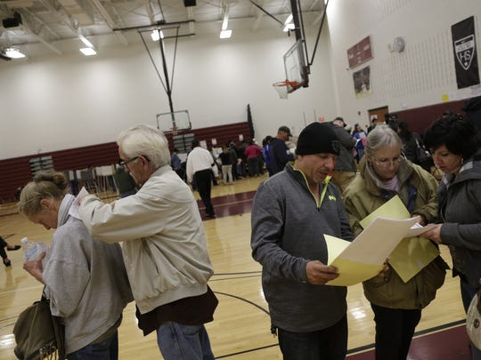 Voters look at their ballots before voting at Western International High School in Detroit, MI on Nov. 8, 2016.