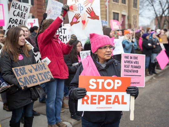 Silvia Tineo-Perez stands next to Planned Parenthood supporters on Saturday, Feb. 11, 2017 in Detroit.
