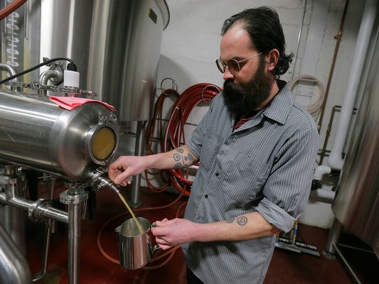 Jason Asch of Asbury Park, head brewer, sample checks an XPA during the first wort, which is beer before it is fermented, at the Asbury Park Brewery in Asbury Park, NJ Wednesday February 15, 2017.