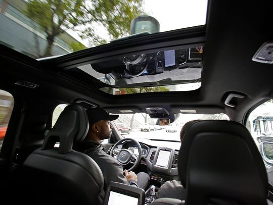 Devin Greene sits in the front seat of an Uber driverless