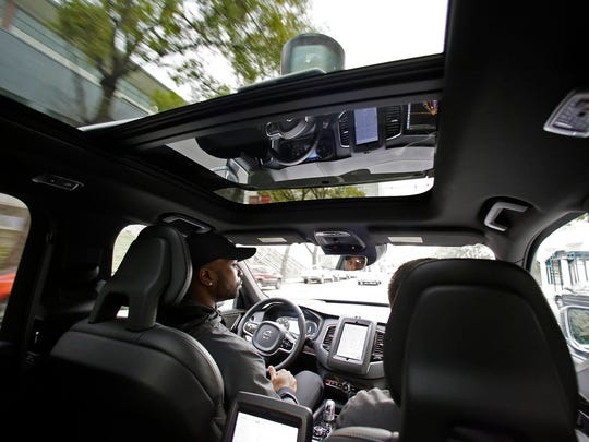 Devin Greene sits in the front seat of an Uber driverless car during a test drive in San Francisco in December 2016.