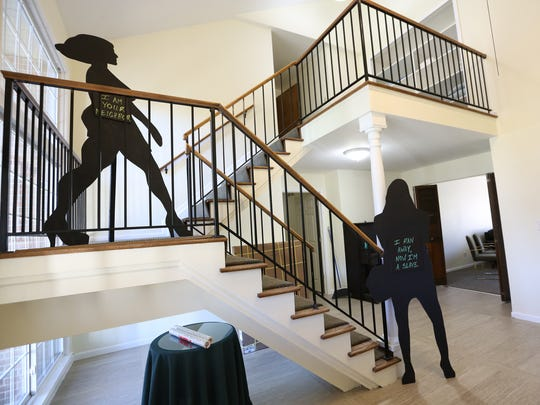 Silhouettes telling the stories of survivors are placed along the stairs leading to the second floor at Sanctum House, a shelter for survivors of human trafficking.