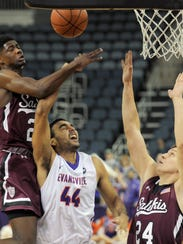 UE's David Howard, 44, (center) has his shot blocked by Southern Illinois' Armon Fletcher, 22, (left) as teammate Rudy Stradnieks, 24, helps on defense (right) on Jan. 14, 2017.