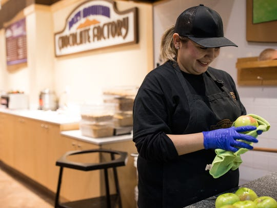 Precious Alvarado cleans apples to make candy apples Thursday, Feb. 16, 2018, at her Rocky Mountain Chocolate Factory store at La Palmera mall in Corpus Christi.