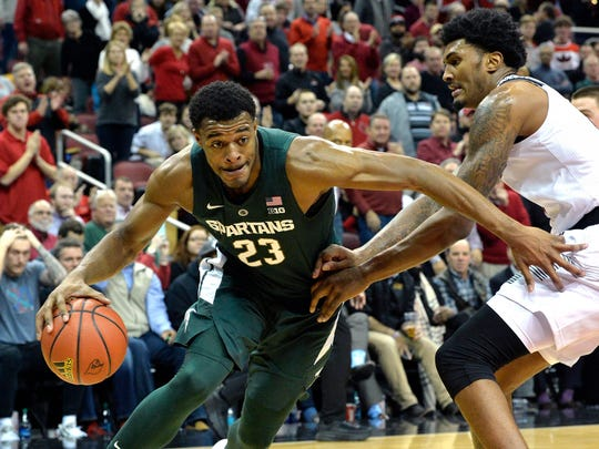 Michigan State forward Xavier Tillman (23) attempts to drive past the defense of Louisville center Malik Williams (5) during the first half of an NCAA college basketball game, in Louisville, Ky., Tuesday, Nov. 27, 2018. (AP Photo/Timothy D. Easley)