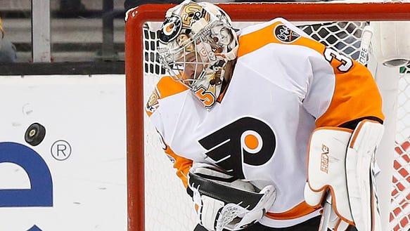 The puck deflects off Philadelphia Flyers' Steve Mason