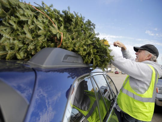 Guy Bytof, a member of the Y-Service Club, secures a Christmas tree to the top of a car while working at the YMCA Christmas tree lot.