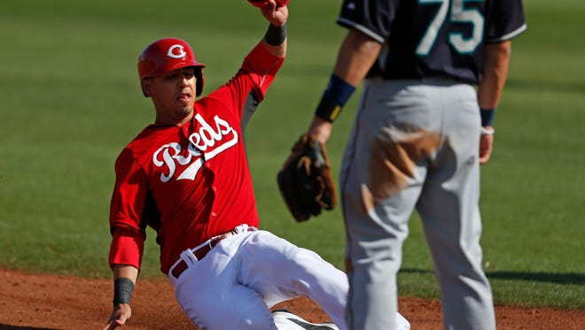 The Reds' Neftali Soto slides into third against the Mariners on March 3.