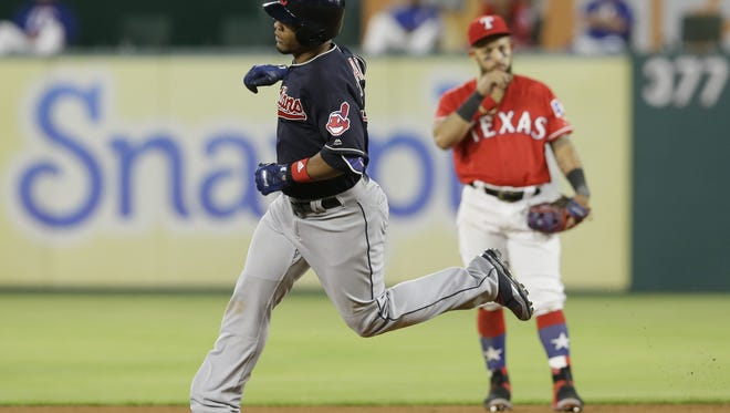 Cleveland Indians Edwin Encarnacion, left, runs the bases past Texas Rangers second baseman Rougned Odor after a solo home run during the eighth inning of an opening day baseball game in Arlington, Texas, Monday, April 3, 2017. The Indians won 8-5. (AP Photo/LM Otero)