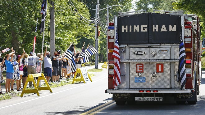A Hingham fire truck flying the thin blue line flag passes police supporters on Central Street in Hingham on Tuesday July 28, 2020. Greg Derr/The Patriot Ledger