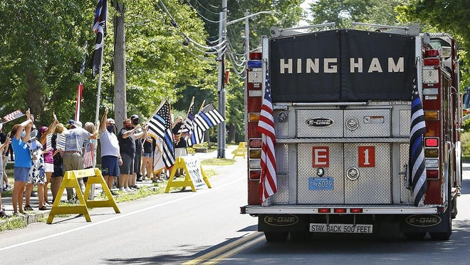 """A Hingham fire truck flying the """"thin blue line"""" flag passes police supporters on Central Street."""