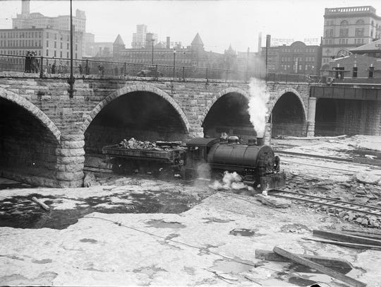 A train running on tracks in the dry Genesee River